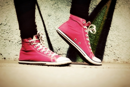 Close up of pink sneakers worn by a teenager. Grunge graffiti wall, retro vintage style photo