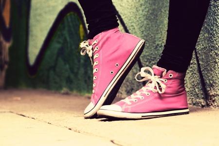 ティーンエイ ジャーが身に着けられてピンクのスニーカーのクローズ アップ。グランジの落書きの壁、レトロなビンテージ スタイル
