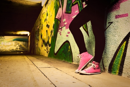 pies bailando: Cerca de zapatillas de color rosa usado por un adolescente. Grunge pared pintada, estilo retro vintage