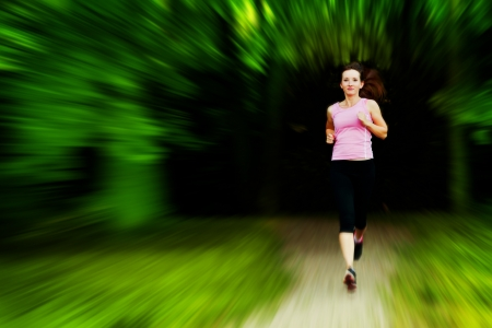 Young fit woman does running, jogging training in a park. Motion photo