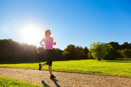 Young fit woman does running, jogging training in a park at summer sunny day