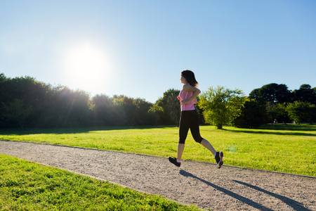 Young fit woman does running, jogging training in a park during sunset photo