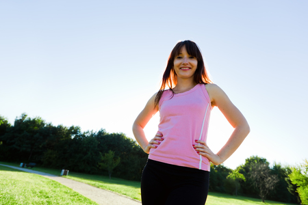 Young fit woman portrait in a park during running, jogging training in a sunny day photo