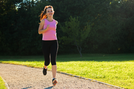 Young fit woman does running, jogging training in a park at summer sunny day photo