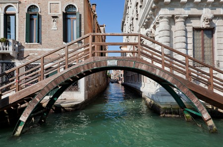 Venice, Italy. A bridge over a narrow canal among old Venetian architecture photo
