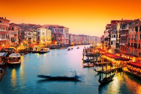 Venice, Italy. Gondola floats on Grand Canal, Italian Canal Grande at sunset. View from Rialto Bridge photo