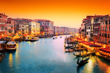 Venice, Italy. Gondola floats on Grand Canal, Italian Canal Grande at sunset. View from Rialto Bridge