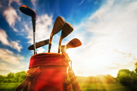 Golf equipment. Professional golf clubs in a leather baggage at sunset