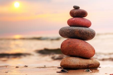 piedras zen: Piedras pirámide sobre la arena simboliza zen, armonía, equilibrio. Océano en la puesta de sol en el fondo Foto de archivo