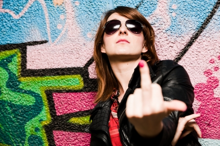 mid teen: Stylish fashionable girl showing fuck off middle finger gesture against colorful graffiti wall.