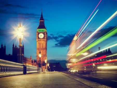 palace of westminster: London, the UK. Red bus in motion and Big Ben, the Palace of Westminster at night. The icons of England