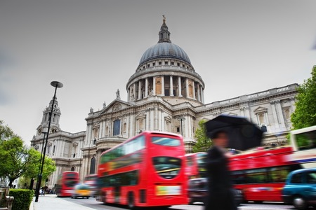 St Pauls Cathedral in London, the UK. Red buses in motion and man walking with umbrella.