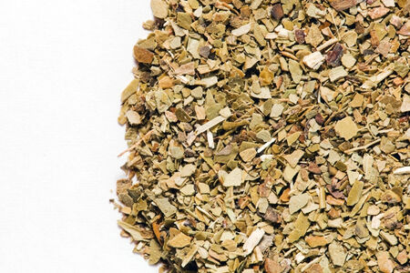 mate drink: Dry Yerba Mate leaves on white background. A popular South American drink known for giving energy and being rich in vitamins.