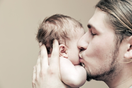 Father with his young baby cuddling and kissing him on cheek  Parenthood, love  Stock Photo
