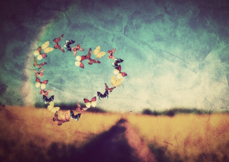 hope: Heart shape made of colorful butterflies on vintage field background  Love, hope concept