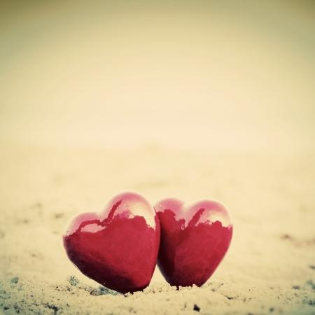 liefde: Twee rode harten op het strand symboliseert liefde, Valentijn Stockfoto