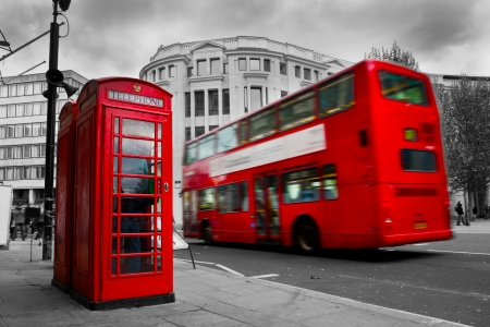 London, the UK  Red phone booth and red bus in motion  English icons photo