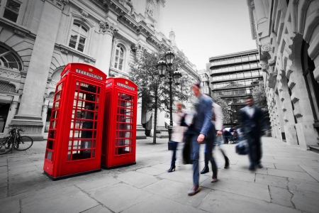 london street: Business life concept in London, the UK  Red phone booth, people in suits walking Stock Photo