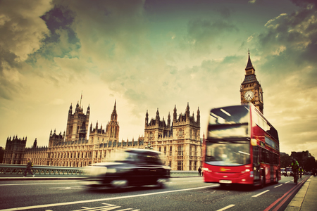 London, the UK  Red bus, taxi cab in motion and Big Ben, the Palace of Westminster  The icons of England in vintage, retro style