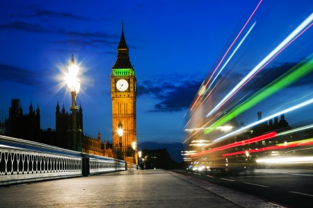 the palace of westminster: London, the UK  Red bus in motion and Big Ben, the Palace of Westminster at night  The icons of England Stock Photo