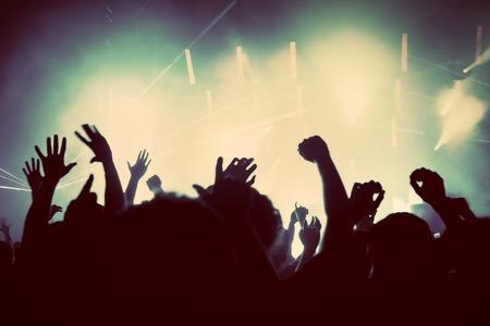 concierto de rock: Las personas con las manos en alto que se divierten en un concierto de música, fiesta disco. Vintage, estilo retro