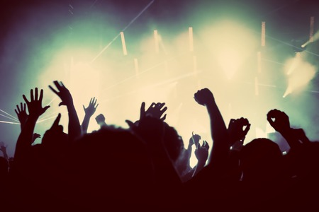 People with hands up having fun on a music concert, disco party. Vintage, retro style photo