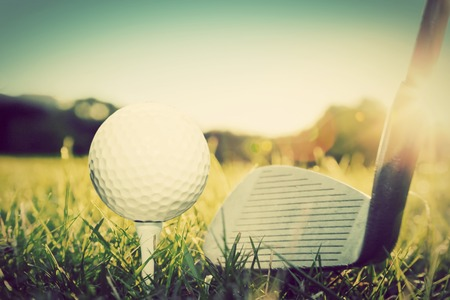 Playing golf, ball on tee and golf club about to shot.\ Vintage, retro style
