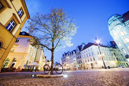 polska monument: Wroclaw, Poland. The market square with historical buildings, tree and bike at night. Silesia region.
