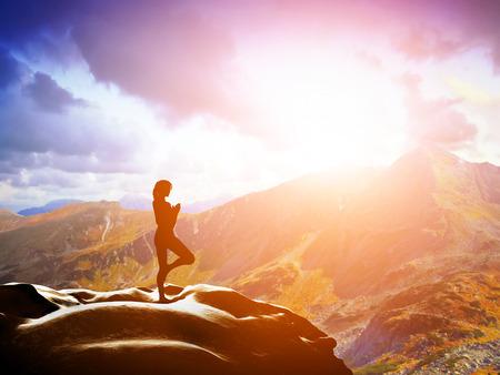 여자 일몰 선에서 산에 바위에, 나무 요가 위치에 서있는 명상, 명상, 평화,