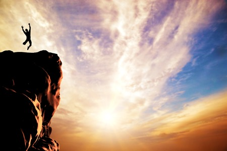 Een silhouet van een man springen van vreugde op de top van de berg, klif bij zonsondergang Succes, winnaar Stockfoto - 26645004