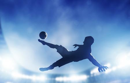 Fotboll, fotboll matcha En spelare skytte på mål utför en cykelspark lampor på stadion på natten Stockfoto