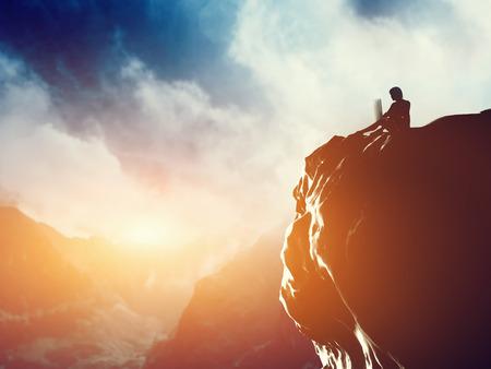 Um homem que trabalha no laptop sentado no pico de uma montanha ao p Imagens