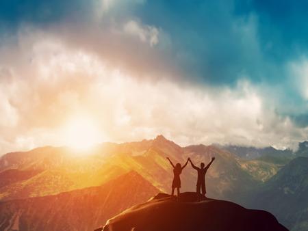 manos levantadas: Una feliz pareja de pie juntos en la cima de una montaña con las manos levantadas admirar impresionantes vistas al atardecer Foto de archivo