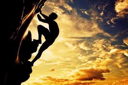 Een silhouet van de mens klimmen op rots, berg bij zonsondergang Adrenaline, moed, leider