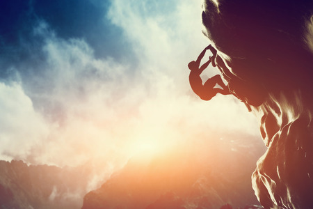 Eine Silhouette des Menschen klettern auf Felsen, Berg bei Sonnenuntergang Adrenaline, Kraft, Ehrgeiz
