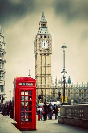 Rode telefooncel en de Big Ben in Londen, Engeland, het Verenigd Koninkrijk Mensen lopen in de spits De symbolen van Londen in vintage, retro-stijl