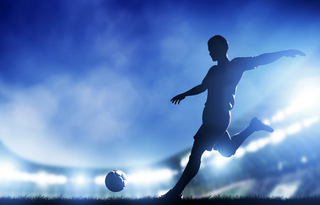 scoring: Football, soccer match  A player shooting on goal  Lights on the stadium at night