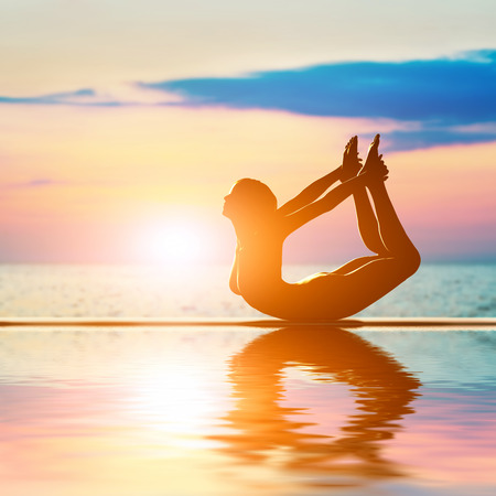 A silhouette of a woman in bow yoga position, meditating against sunset sky  Zen, meditation photo