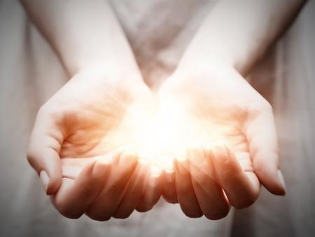 волшебный: Свет в молодых руках женщины в Чашевидный форме. Концепции совместного, давая, предложение, заботящиеся, защиту