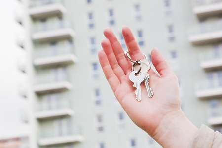 selling house: A real estate agent holding keys to a new apartment in her hands. Real estate industry