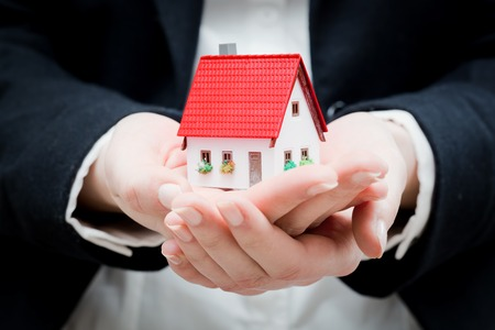 hands holding house: A real estate agent holding a small new house in her hands. Conceptual