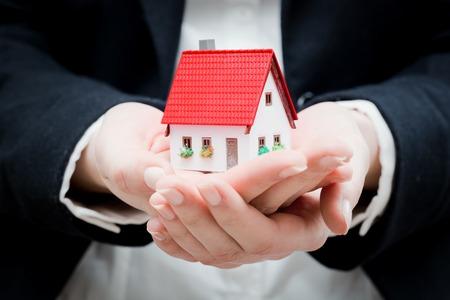 Een makelaar die een klein nieuw huis in haar handen. conceptuele Stockfoto