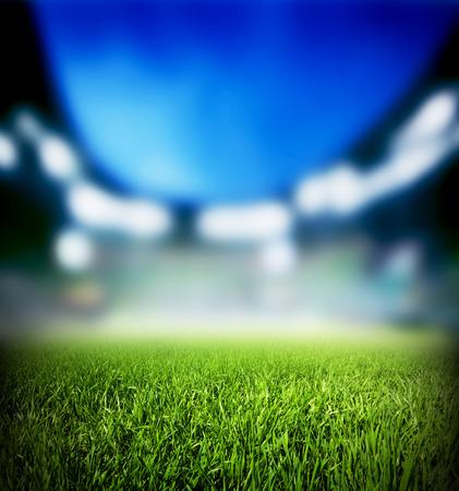サッカー、サッカーの試合。草をクローズ アップ。夜のイベント、競技場が点灯します。
