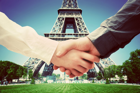client meeting: Business in Paris, France. Handshake on Eiffel Tower background. Deal, success, contract, cooperation concepts  Editorial