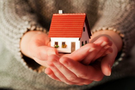selling house: Woman holding a small new house in her hands. Real estate, mortgage, housing concepts etc.