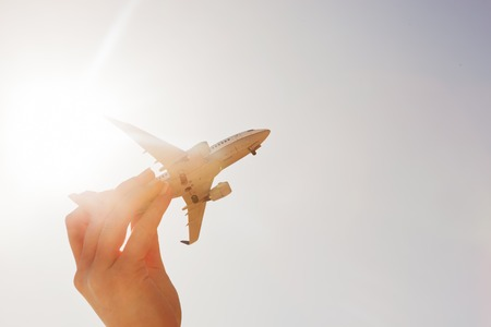 Airplane model in hand on sunny sky. Concepts of travel, transportation, transport, dreaming about holidays