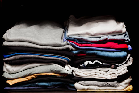 PIles of various clothes from laundry in a wardrobe. Black background photo