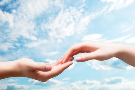 Man and woman hands touch in gentle, soft way on blue sunny sky. Concepts of connection, hope, faith, help, love. photo