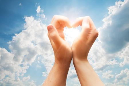 simbolo uomo donna: L'uomo e la donna mani fanno una figura del cuore sul blu cielo soleggiato. Amore, emozioni, felicità. Archivio Fotografico
