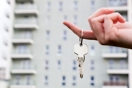 apartment buildings: A real estate agent holding keys to a new apartment in her hands. Real estate industry